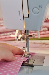 A hand of a dressmaker supporting fabric while sewing on a sewing machine