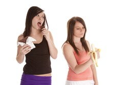 a woman licking and enjoying her chocolate bar while her friend eats a banana.