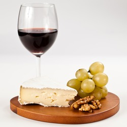 Piece of Brie french cheese with grapes and nuts over an hearth shaped wooden board and a glass of red wine in isolated studio shot