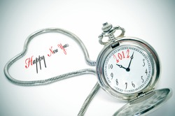 sentence happy new year and a pocket watch number 2012 inside it