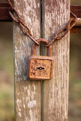 Old vintage rusty padlock and chain on the wooden door.