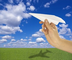 Paper airplane made in flight against a background of beautiful landscape