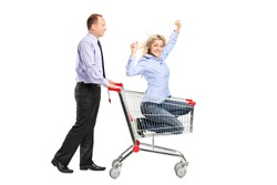 Person pushing a happy woman in a shopping cart isolated against white background