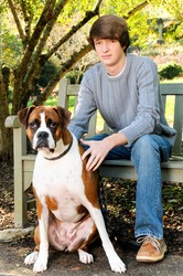 Teenage boy with his Boxer dog sitting on a park bench