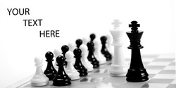 White and black king on the chessboard opposing each other,black and white pawns in the background,can be used as concept for conflict, meeting, agreement..