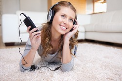 Young woman lying in the living room enjoying music