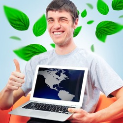 Portrait of young man sitting indoors at his office and working. Green leaves are floating around him. Business using Green power concept.