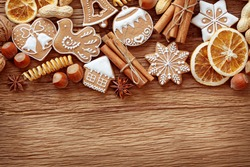 Gingerbread cookies and spices over wooden background close up