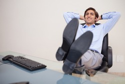 Smiling young businessman leaning back in his chair