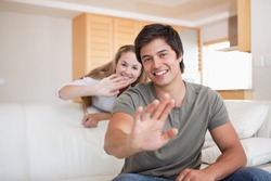 Couple waving at the camera in their living room