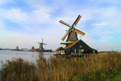 a dutch landscape with a mill and green grass field and river in view (holland, zaanse schans)