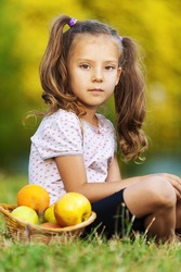 pretty sad portrait of child ( girl), sitting on green grass (meadow) with wicker basket with fruits (apples, oranges)