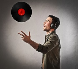 Young deejay wearing headphones and throwing a vinyl disc