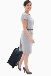 Side view of smiling woman with wheely bag against a white background