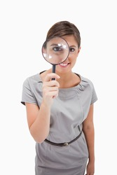 Woman using magnifier against a white background