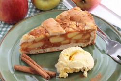 A slice of apple pie with a lattice pastry crust. Decorated with cinnamon sticks and fresh apples.