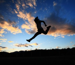 man jumping againts dark blue sky background.