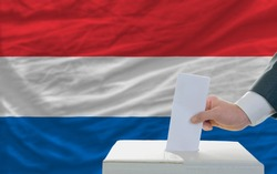 man putting ballot in a box during elections in netherlands in fornt of flag