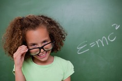 Smart schoolgirl looking above her glasses in front of a blackboard