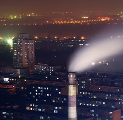Photo of night scene of chimney with smoke in residents area in heavy fog