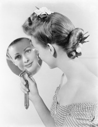 Reflection of a young woman, looking in a mirror