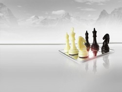 Chess pieces on white reflective foreground with abstract winter mountain scape in background