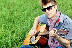Portrait of a handsome young man with a guitar outdoor.