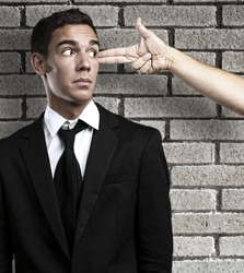 man gesturing a gun pointing at a business man against brick wall background