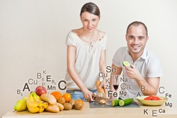 Young lovely couple cooking a balanced diet. Big copyspace. Vitamins and microelements symbols are around them.