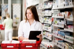 Female pharmacist working in pharmacy with digital tablet and medicine