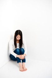 attractive asian woman sitting corner of all white room