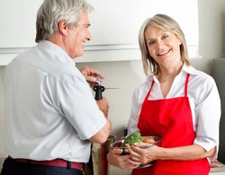 Happy senior couple cooking together in kitchen