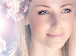 Sensual portrait of a spring woman, beautiful face female enjoying cherry blossom, dreamy girl with pink fresh flowers outdoor, seasonal nature, tree branch and glamorous lady