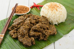 Beef Rendang & Sticky Rice - Malaysian / Indonesian spicy dry beef stew with coconut and sticky rice served on a banana leaf.