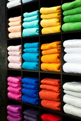 Wooden shelf full of colored fluffy towels