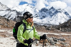 Young woman trekking in Himalaya Mountains, Nepal. Sport and fitness in autumn nature. Travel and trekking destination for tourists and trekkers