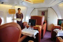 SINGAPORE - FEBRUARY 12: First class cabin with Singapore girl in Singapore Airlines' (SIA) last Boeing 747-400 aircraft at Singapore Airshow February 12, 2012 in Singapore