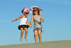 Two little sisters cheerfully jumping on the sand
