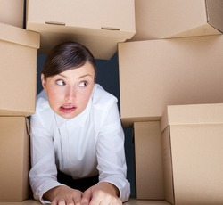 Portrait of young woman surrounded by lots of boxes. Lots of work concept.