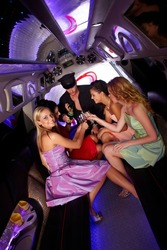 Party time in limousine with elegant young girls and chauffeur, drinking champagne.?