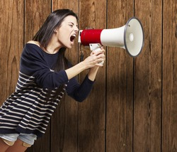 young woman shouting with a megaphone against a wooden background