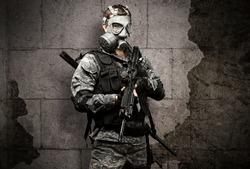 portrait of a young soldier with a gas mask and rifle against a grunge brick background