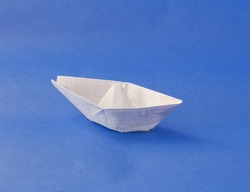 Little white paper boat over blue background