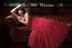 Woman in red evening dress lying on the sofa