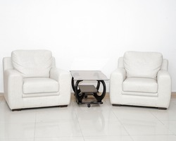 Detail of a modern living room with white armchair and glass coffee table