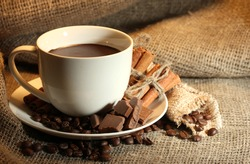 cup of coffee and beans, cinnamon sticks and chocolate on sacking background