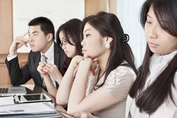 Group of business people look bored during meeting
