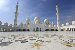 The courtyard of Sheikh Zayed Grand Mosque in Abu Dhabi with two minarets.