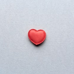 Red satin heart. Closeup on gray textured paper.
