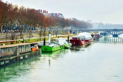 Dramatic HDR rendering of a beautiful scene or landscape of houseboats or barges with their freight along the banks of the Rhone river, Lyon, France on a misty morning.